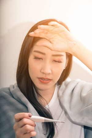 Asian woman sick from cold and used with thermometer suffering on sofa in the room.