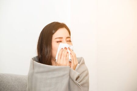 Asian women with stress that suffer from allergies and close the nose with tissue paper. Because of having sneezing all the time.