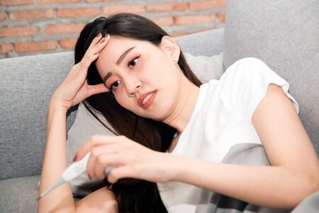 Pretty Asian woman sick from cold and used with thermometer lying on sofa in the room.