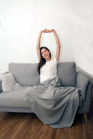 Asian woman relaxed and resting breathing fresh on sofa at home. Archivio Fotografico
