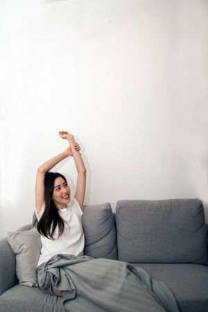 Donna asiatica rilassata e riposata respirando fresca sul divano di casa.