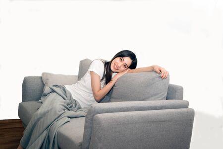 Donna asiatica rilassata e riposata respirando fresca sul divano di casa. Archivio Fotografico