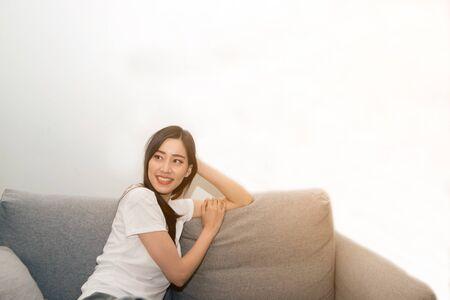 Asiatische Frau entspannt und ruht sich zu Hause frisch auf dem Sofa aus.