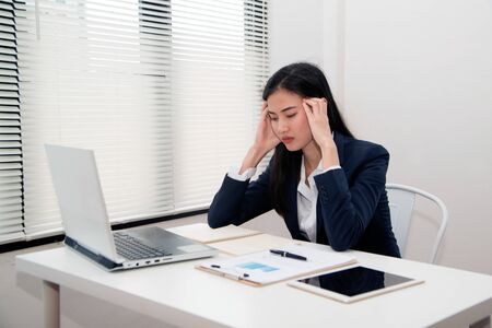 Asian Young beautiful business woman suffering stress working at office from feeling tired and desperate looking overworked and overwhelmed and frustrated.