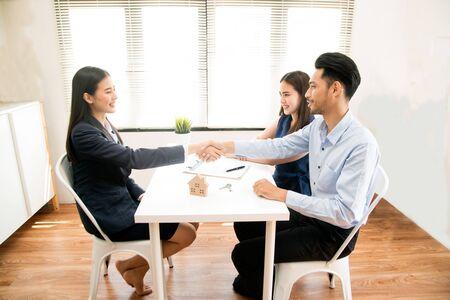 Geschäftsfrau, die Hand mit einem jungen Paar im Büro rüttelt. Bankagent und sein Kunde schütteln sich im Konferenzraum die Hände. Glücklich lächelnde Paare schließen einen Deal mit ihrem persönlichen Finanzberater ab.