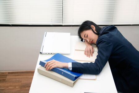Young Asian business woman Sleep on table in office because over working , stressed from work overload and is a tired and sleepy lady.
