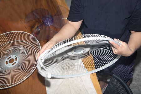 Housewife use white cloth Wipe and clean the electric fan.