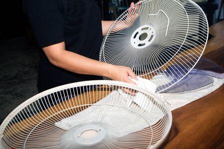 La femme au foyer utilise un chiffon blanc Essuyez et nettoyez le ventilateur électrique. Banque d'images