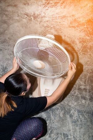 The housekeeper is assembling and installing an electric fan after cleaning.