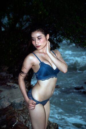 Pretty Asian woman in blue bikini posing on the beach with fun.