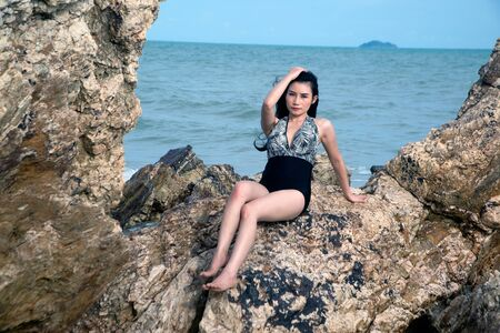 Pretty Asian woman in swimming suit posing on the stone of beach with fun.
