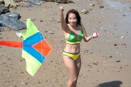 Asian women in swimming suits are playing colorful kite for fun. She is an Asian traveler, a beautiful woman in a bikini posing on the beach.