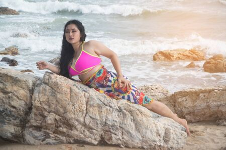 Asian plus size fat and overweight woman in a swimming suit lie on the stomach on rock and strong waves on the beach. Фото со стока