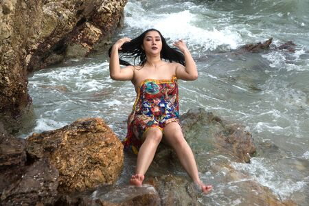Asian plus size fat and overweight woman in a swimming suit sitting on rock and strong waves on the beach. Фото со стока