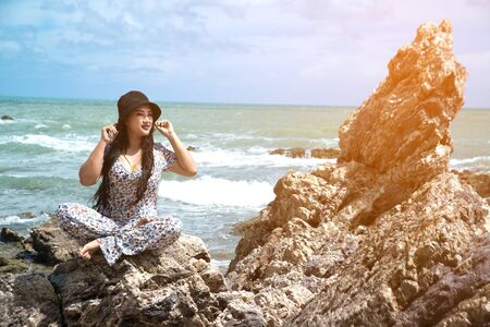 Asian plus size fat and overweight woman in a colorful dresses sitting on rock at the beach. Фото со стока