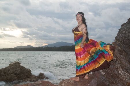 Asian plus size fat and overweight woman in a colorful dresses standing on rock at the beach. 写真素材