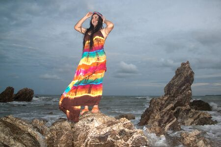 Asian plus size fat and overweight woman in a colorful dresses standing on rock at the beach. Фото со стока