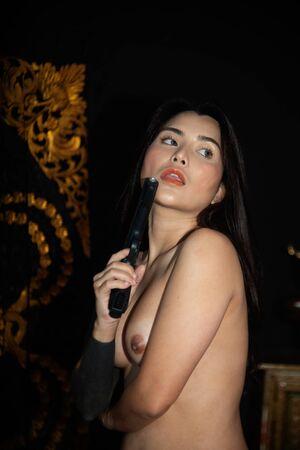 Portrait pretty Asian sensuality model pose holding gun in studio shot.