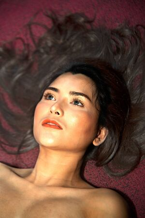 Pretty Sensual nude Asian women sensuality lying on the red floor.