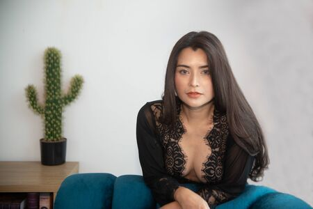 Sensual sexy dresses Asian women sensuality arm on the blue sofa. Banque d'images