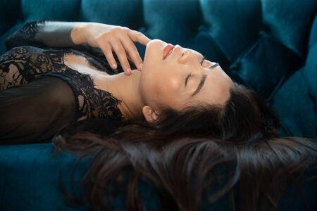 Sensual sexy dresses Asian women sensuality lying on the blue sofa.