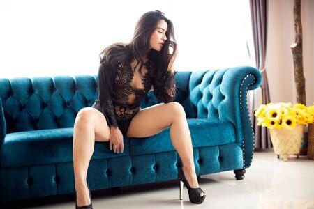 Sensual sexy dresses Asian women sensuality sitting on the blue sofa. Stock Photo