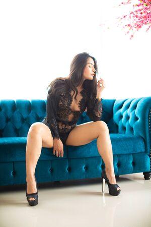 Sensual sexy dresses Asian women sensuality sitting on the blue sofa. Archivio Fotografico