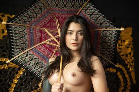Sensual sexy nude Asian women sensuality standing and hold a umbrella front of art wall. Stock Photo