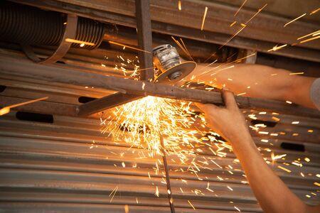 Der Arbeiter sägt und schneidet Metallteile von Werbetafeln aus Stahl in einem Geschäft.