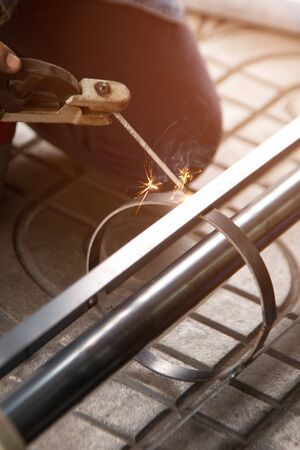 The worker is welding metal part of the details of the system rolling lifting gate. Selective focus. Stock fotó