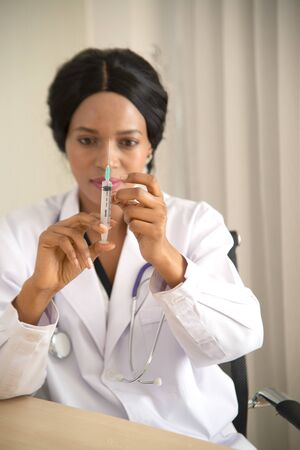 An African female doctor holds a syringe and tries to expel the needle in the concept of health care.