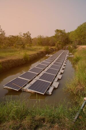 Solar power generation panel Installed on the water in the pond, reflecting the sun and blue sky Which is the most productive use in a limited area. Stock Photo