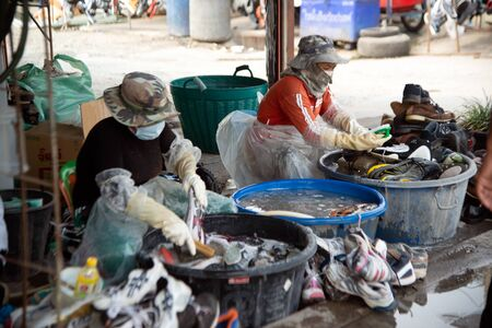 SA KAEO, THAILAND - FEBRUARY 5, 2020: An unidentified worker is washing used sneakers in the water. And wear a Corona virus protection mask and small dust, pm.2.5, awaiting future sales on Rong Kluea market in Sa Kaeo Province Thai-Cambodian border.