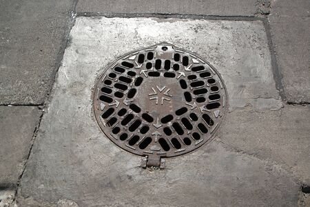 Manhole cover has rust on the street.