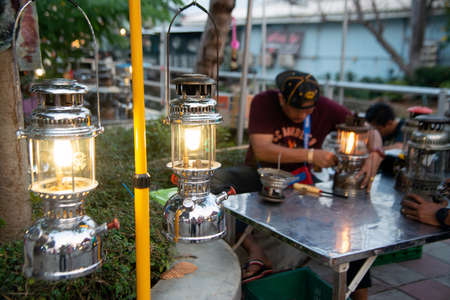 NAKORN PATHOM, THAILAND - FEBRUARY 22 , 2020 : Unidentified male is repairing the old hurricane lamp To be shown at the Hurricane lamp show 2020 event at Don Wai floating market in Nakorn Pathom Province , Middle of Thailand. 新聞圖片