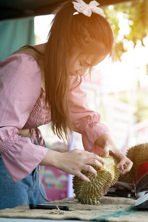 Asian pretty woman tearing durian by hand, durians, often called the king of fruits peels fruits. It is a big fruit with a strong smell & a hard shell with sharp thorns.