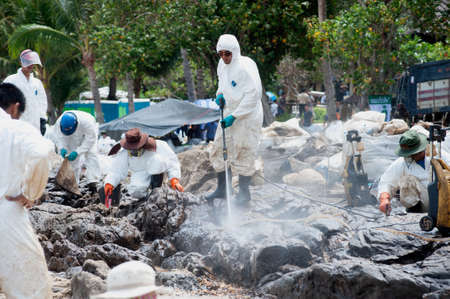 RAYONG,THAILAND-FEBRUARY 8,2013 : Unidentified Workers and volunteers are spraying chemicals onto crude oil contaminated on the beach at Prew beach, on Samet island , Khao Laem Ya-Mo Ko samet National Park in Thailand. Editorial