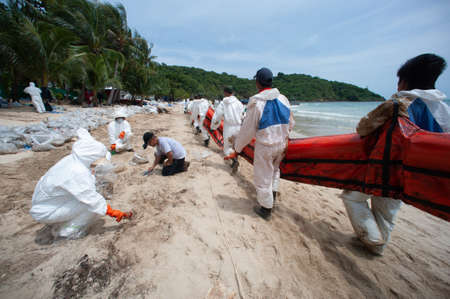 RAYONG,THAILAND-FEBRUARY 8,2013 : Unidentified Volunteers line up to put the plastic pallet in the sea near Prew beach In order to block crude at Samet island , Khao Laem Ya-Mo Ko samet National Park in Thailand. Editorial