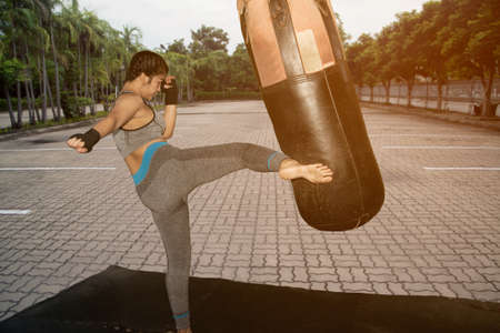 Beautiful young Asian white girl with long hair 20-30 years old. practice Muay Thai boxing by kicking at Boxing Sandbag at the park. Banque d'images