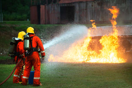 Firefighters spraying water to put out a brutal fire on the truck. Фото со стока