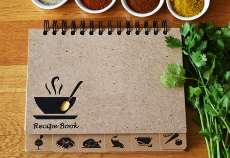 flavorsome: Notebook for recipes and spices on wooden table with coriander. Stock Photo