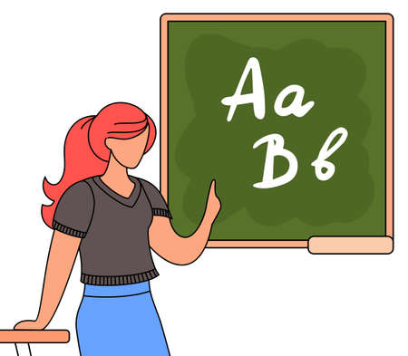 Young red-haired woman teacher with ponytail lean on table standing near school board, gesturing hand. Teacher telling about letters of alphabet or calligraphy. Studying grammar at lesson at school