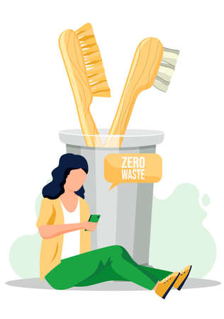 The girl sits on the floor with a smartphone in her hands and writes sms or sends an email. Natural organic wooden toothbrushes in a glass beaker. Zero waste, eco friendy equipment for oral hygiene