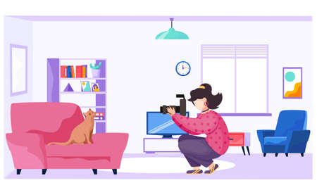 Female photographer makes pictures of a kitten sitting on the armchair. Girl with the camera takes pictures of the pet. Photo session of animal. Shooting in apartment. Cat as an experienced model