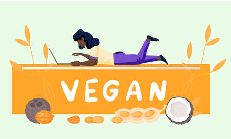 A girl with a laptop lies on an orange lettering and works or studies on her computer. Vegan concept. Freelance woman with ears of wheat on background. Coconut, walnuts, peanuts. Healthy lifestyle