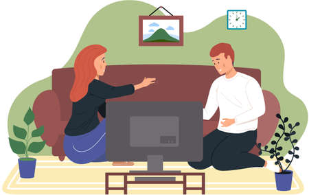 The couple is sitting at home and watching TV. Young people communicate and spend time together. The girl looks at her boyfriend and holds his hand. Joint viewing of cinema in the apartment