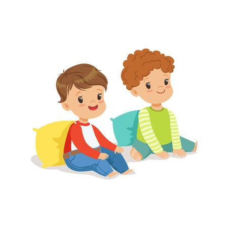 Zwei süße lächelnde kleine Jungen, die auf dem Boden sich lehnt auf Kissen, bunter Charakter sitzen Standard-Bild - 82899559