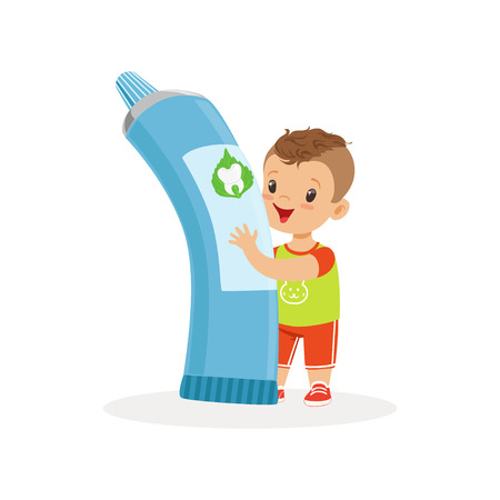 Cute little boy standing and holding big tube of toothpaste, cute cartoon character vector Illustration on a white background