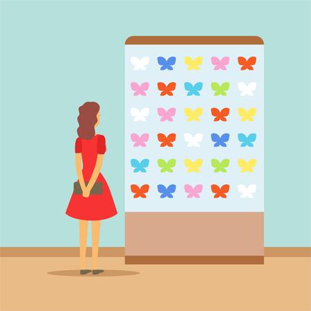 博物館での展示会で蝶を見ている若い女性