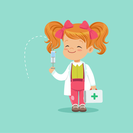 Cute red-haired baby girl standing with medical suitcase and syringe in hands. Child in white coat and pink bows on head playing doctor game